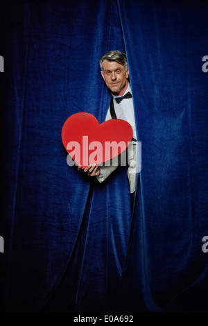 Man behind curtain with big red paper heart - Stock Photo