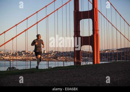 Young man out running near golden gate bridge - Stock Photo