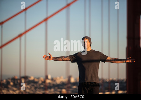 Young male runner with open arms in front of golden gate bridge - Stock Photo