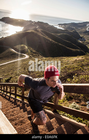 Young man running up coastal staircase - Stock Photo