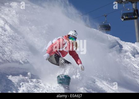 Young woman snowboarding on steep mountain, Hintertux, Tyrol, Austria - Stock Photo