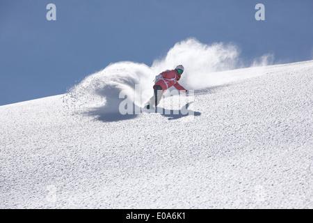 Young woman snowboarding on mountain, Hintertux, Tyrol, Austria - Stock Photo