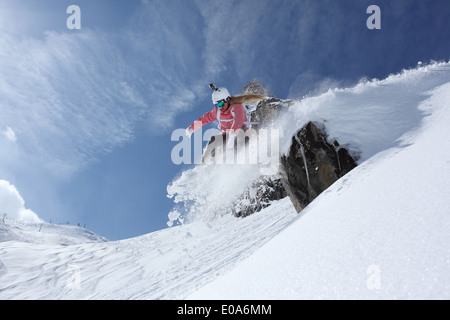 Young female snowboarder jumping off ledge on mountain, Hintertux, Tyrol, Austria - Stock Photo