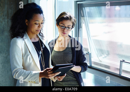 Two businesswomen looking at digital tablet in office - Stock Photo
