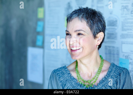 Portrait of smiling mature businesswoman in office - Stock Photo