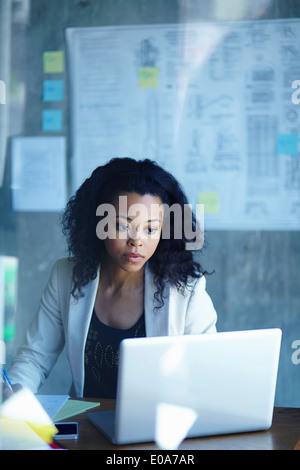 Young businesswomen working on laptop in office - Stock Photo