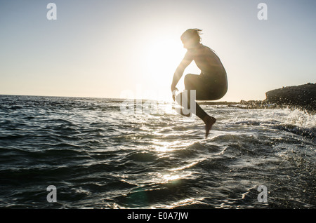 Teenage boy jumping in the sea - Stock Photo
