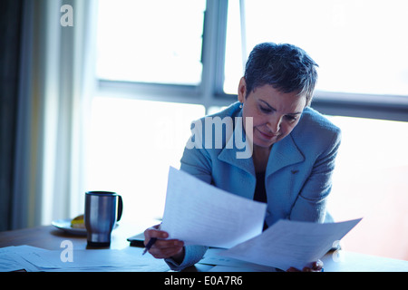 Mature businesswoman reading paperwork in office - Stock Photo