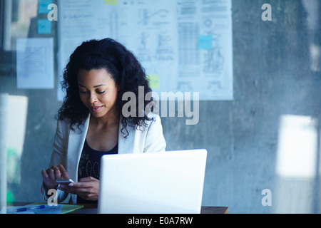Young businesswomen texting on smartphone in office - Stock Photo