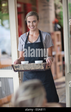 Young female waitress carrying tray of coffee cups in cafe - Stock Photo