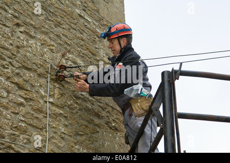 Male electrician on platform fixing house electricity supply - Stock Photo