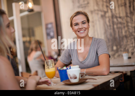Two young adult female friends enjoying a chat in cafe - Stock Photo