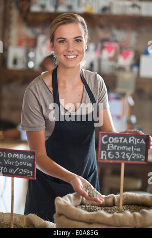 Portrait of young female waitress holding coffee beans in cafe - Stock Photo