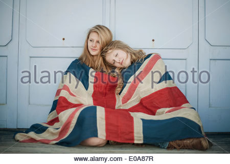 Portrait of sisters sitting on porch wrapped in union jack flag - Stock Photo