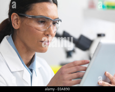 Scientist viewing test results on a digital tablet in lab - Stock Photo