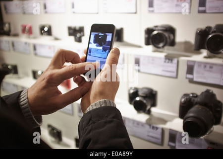 Mid adult man photographing camera's in shop display using smartphone - Stock Photo