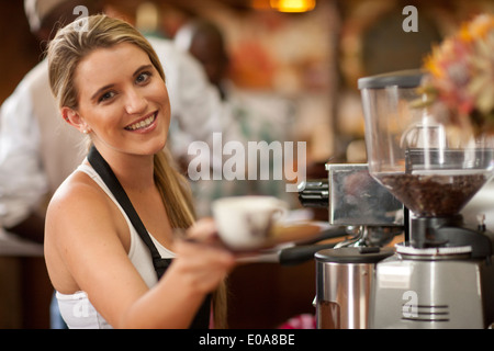 Portrait of young woman preparing cup of coffee in cafe - Stock Photo