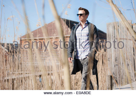 Mid adult man walking along pier with hand in pocket - Stock Photo