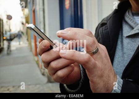 Mid adult man on sidewalk using touchscreen on smartphone - Stock Photo