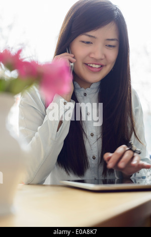Woman using phone and digital tablet - Stock Photo