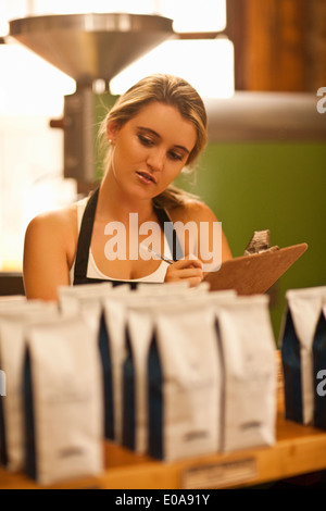 Young woman working in coffee shop, holding clipboard