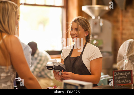 Young woman serving customer in coffee shop - Stock Photo