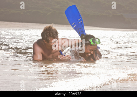 Young couple lying in sea, wearing snorkel - Stock Photo