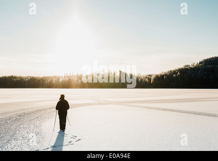 Mature man nordic walking through snow covered field - Stock Photo