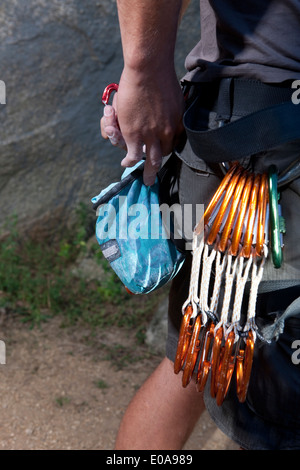 Cropped shot of young male climber attaching carabiners to belt - Stock Photo