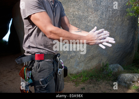 Cropped shot of young male climber rubbing sports chalk on hands - Stock Photo