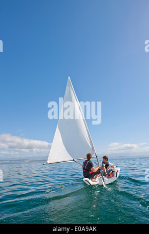Two young men sailing out to sea - Stock Photo