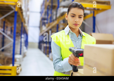 Young woman with barcode reader in distribution warehouse - Stock Photo