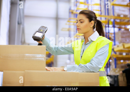 Young woman using barcode reader in distribution warehouse - Stock Photo