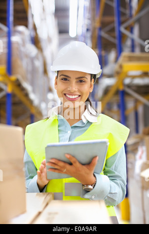 Young woman with digital tablet in distribution warehouse - Stock Photo