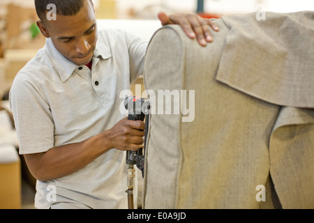Upholsterer attaching textile to sofa using staple gun - Stock Photo