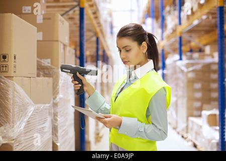 Female warehouse worker using barcode reader - Stock Photo