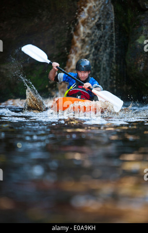 Mid adult man kayaking on river - Stock Photo