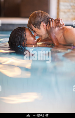 Romantic young couple in spa swimming pool - Stock Photo