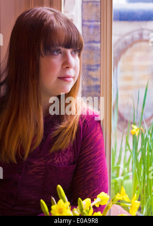 Portrait of girl by window - Stock Photo