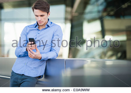 Mid adult man leaning against wall reading texts on smartphone - Stock Photo