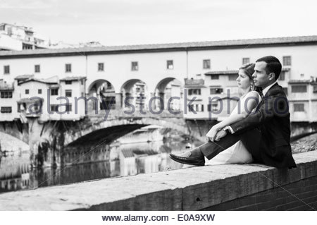 Couple sitting on wall beside river in Florence, Tuscany, Italy - Stock Photo