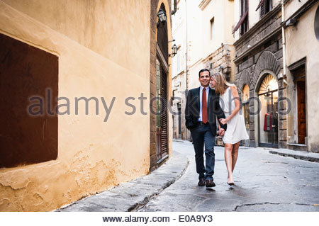 Couple holding hands, walking down street in Florence - Stock Photo