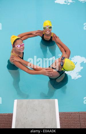 Portrait of three schoolgirl swimmers making circle - Stock Photo