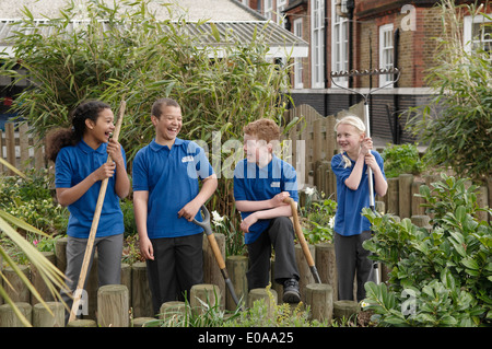 Group of four school children with gardening tools - Stock Photo