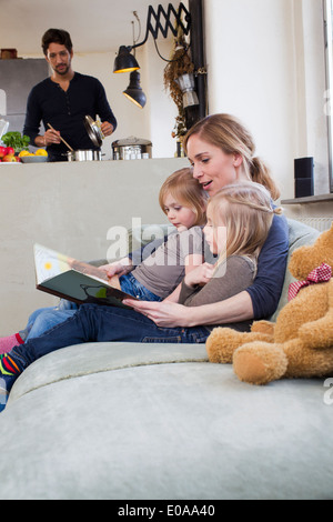Mother and two daughters reading storybook - Stock Photo