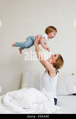 Portrait of mid adult woman holding up her one year old baby girl - Stock Photo