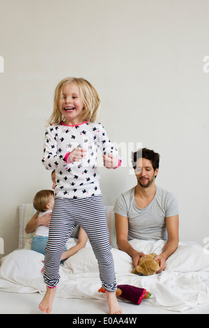 Young girl jumping on her parents bed - Stock Photo
