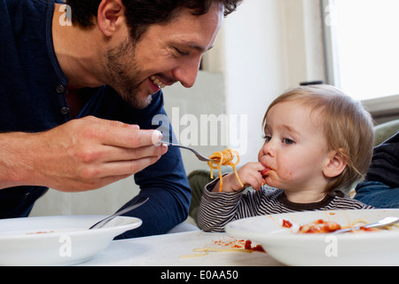 Father feeding one year old daughter spaghetti - Stock Photo