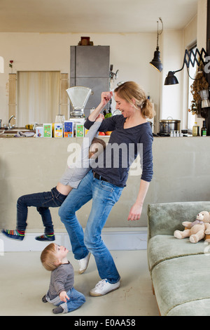Mid adult mother playing with her two young daughters - Stock Photo