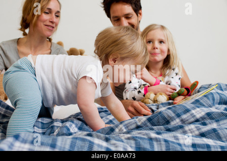 One year old baby girl crawling on parents bed - Stock Photo
